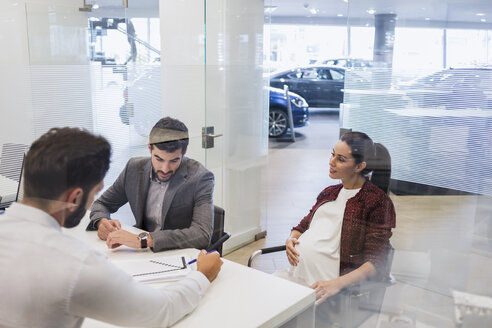 Car salesman explaining financial contract paperwork to pregnant couple customers in car dealership office - CAIF20006