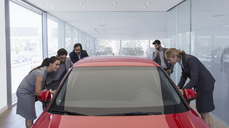 Customers looking at new car in car dealership showroom - CAIF20024