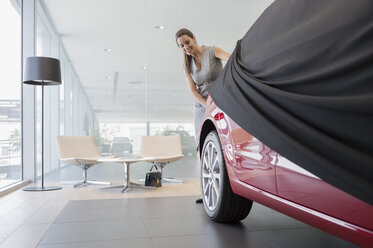 Car saleswoman removing cover from new car in car dealership showroom - CAIF20072