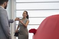 Car salesman handing car keys to smiling female customer in car dealership showroom - CAIF20090