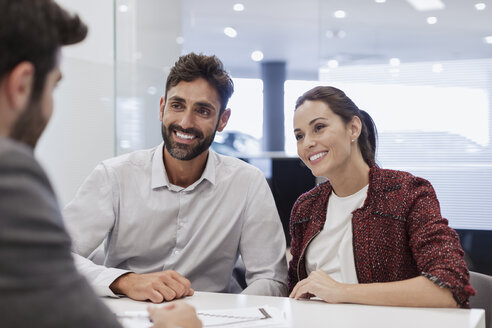 Smiling couple customers talking to car salesman in car dealership office - CAIF20096