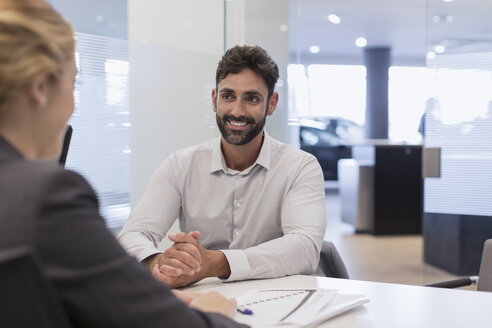 Smiling male customer listening to car saleswoman in car dealership office - CAIF20099