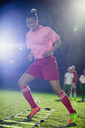 Young female soccer players practicing agility sports drill on field at night - CAIF20120