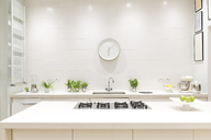 White, modern luxury home showcase interior kitchen with clock - CAIF20153