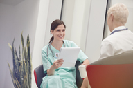 Smiling female nurse with clipboard talking to doctor in hospital - CAIF20156