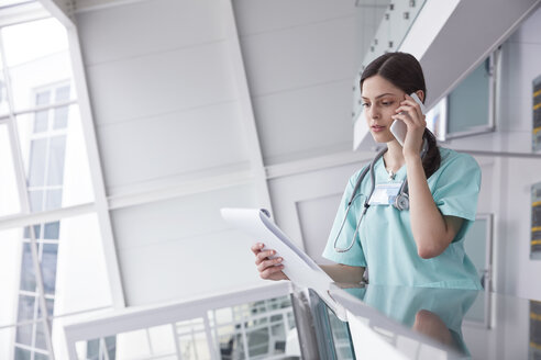 Female nurse with clipboard talking on cell phone in hospital - CAIF20183