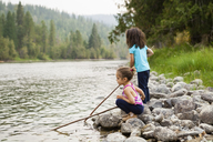 Girl sisters playing with sticks at lakeside - CAIF20204