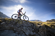 Low angle view of cyclist with bicycle on mountain against sky - CAVF17849