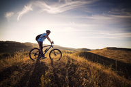 Male athlete on bicycle in grassy field against cloudy sky - CAVF17876