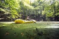 Man oaring boat on swamp in forest - CAVF17882