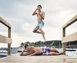 Shirtless brothers enjoying at pier over sea against sky - CAVF17981