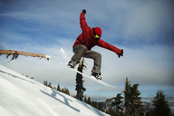 Male snowboarder jumping on snowcapped mountain against sky - CAVF18044