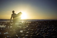 Man with surfboard walking at beach against sky during sunset - CAVF18071
