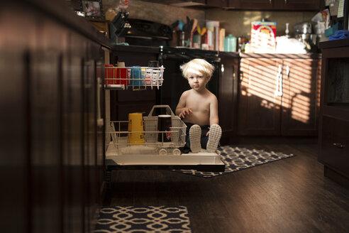 Portrait of boy sitting on drawer in kitchen - CAVF18113