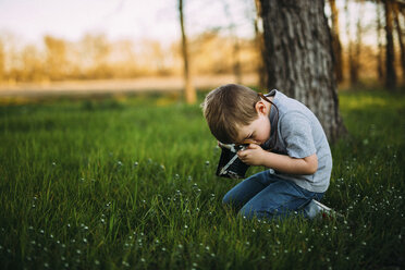 Side view of boy photographing through vintage camera - CAVF18143