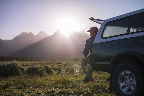 Man looking away while sitting on off-road vehicle at Grand Teton National Park - CAVF18284