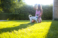 Woman kneeling while playing with dog on grassy field at backyard - CAVF18326