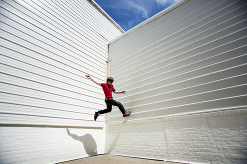 Low angle view of man jumping on white wall - CAVF18824