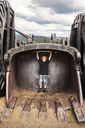 Happy boy standing in metal container at field - CAVF18827