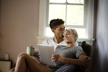 Man kissing woman using tablet computer at home - CAVF18878