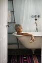Side view of thoughtful woman holding drink glass while relaxing in bathtub at home - CAVF18902
