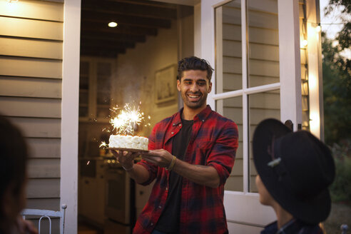 Happy man holding birthday cake with sparklers - CAVF18920