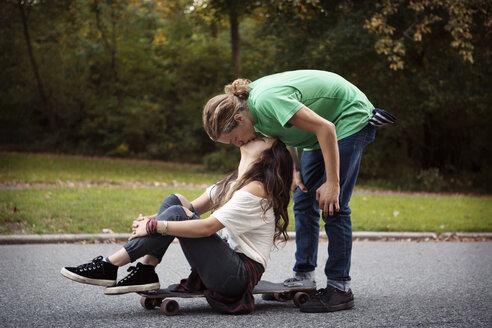 Man kissing woman sitting on skateboard at street - CAVF19010