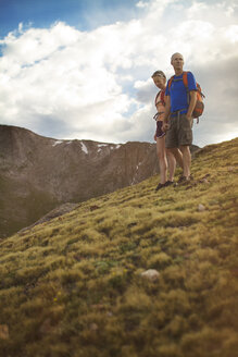 Low angle view of couple standing on mountain against cloudy sky - CAVF19322