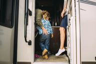 Mother embracing daughter while standing with husband in camper van - CAVF19673