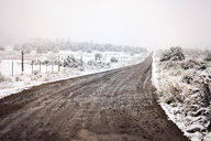 Wet dirt road amidst snow covered field during foggy weather - CAVF19730