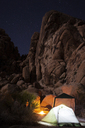 Illuminated tents against rock formations at night - CAVF19733