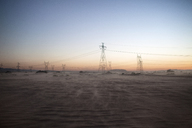 Electricity pylons on field against clear sky during sunset - CAVF19736