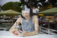 Smiling woman using phone while having drink at restaurant seen through window - CAVF19784