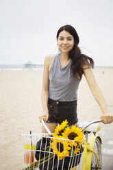 Portrait of smiling woman standing with bicycle at beach - CAVF19793