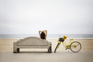Rear view of woman sitting on bench by bicycle at beach against clear sky - CAVF19796
