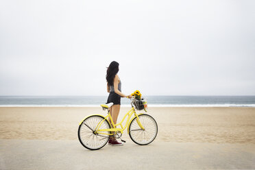 Woman standing with bicycle at beach against clear sky - CAVF19799