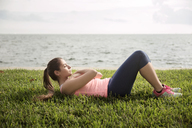 Side view of woman exercising on grassy field against sea - CAVF19865