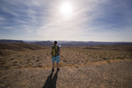 Rear view of hiker standing on field against sky during sunny day - CAVF19892