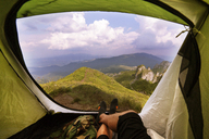 Low section of man lying inside tent against mountains - CAVF19901