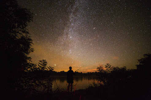 Silhouette man fishing at lakeshore against starry sky during night - CAVF19910