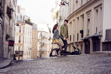 Young couple talking while crossing street in city - CAVF19922