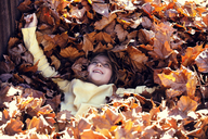 High angle view of girl lying on autumn leaves at field - CAVF20060