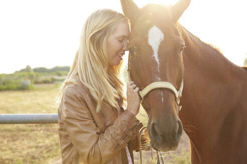 Happy woman stroking horse in farm - CAVF20081
