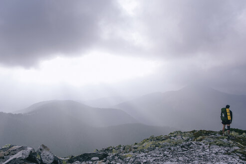 Full length of hiker standing on mountain during foggy weather - CAVF20138