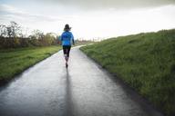 Full length of female athlete running on road amidst grassy field - CAVF20201