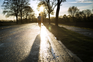 Rear view of male athlete running on road during sunset - CAVF20222