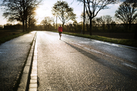 Mid distance of woman running on road during sunset - CAVF20225