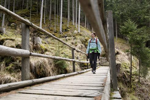 Female hiker walking on boardwalk in forest - CAVF20333
