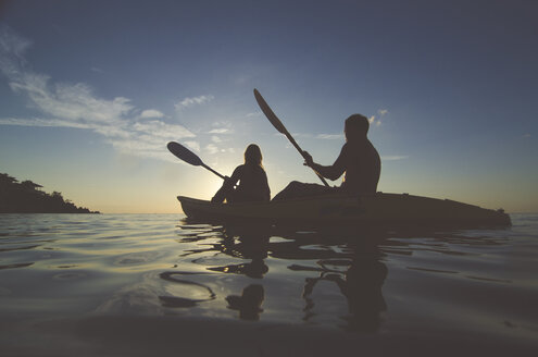 Silhouette friends kayaking on sea against sky during sunset - CAVF20378