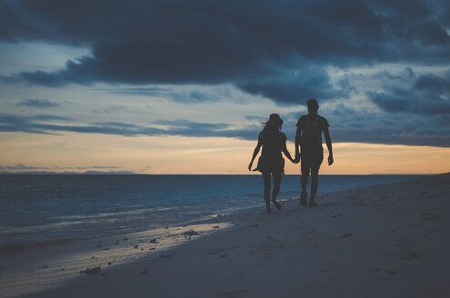 Silhouette couple holding hands and walking at beach against cloudy sky during sunset - CAVF20381
